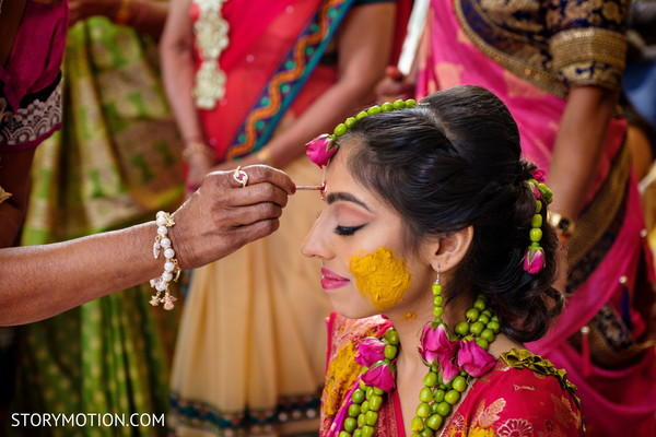 Indian bride getting the red dot on forehead.