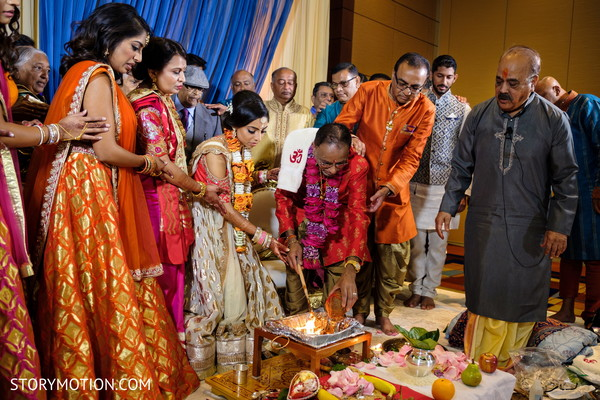 Indian bridal parents making offering to sacred fire.
