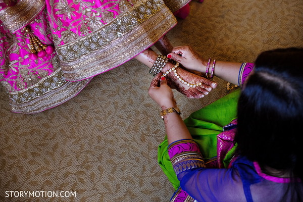 Indian bride putting her anklets on.