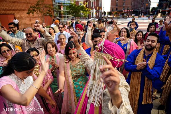 Upbeat Indian grooms dancing at baraat.