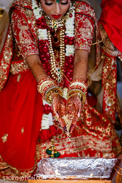 Ritual where Indian bride throws rice in sacred fire.