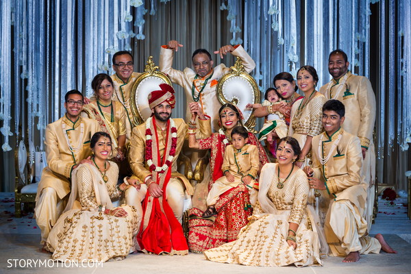 Graceful Indian bride and groom posing with family.