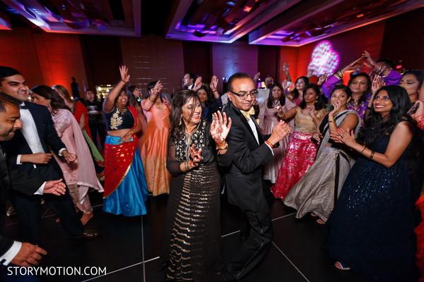 Joyful indian wedding guests dancing.