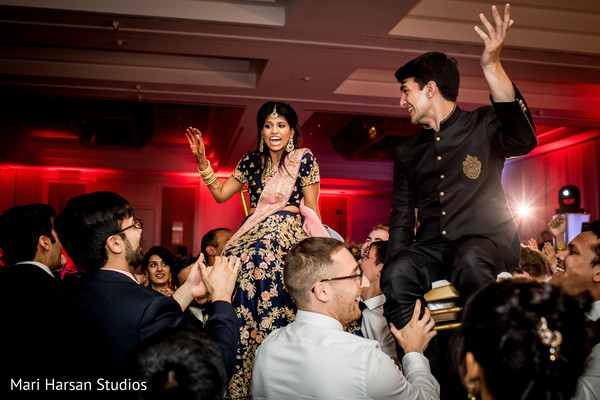 Indian newlyweds being lifted by joyful guests