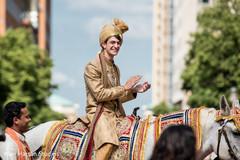 Happy indian groom riding baraat horse
