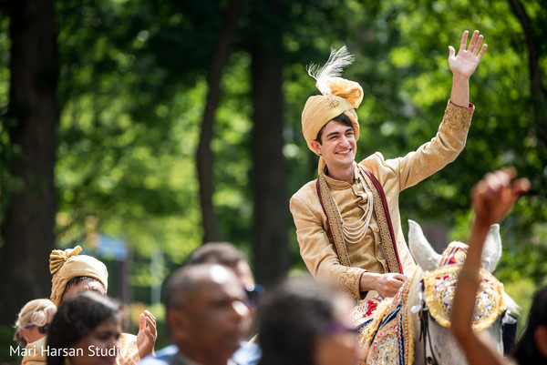 Handsome indian groom riding baraat horse