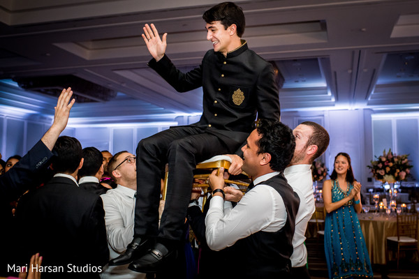 Indian groom being lifted by guests