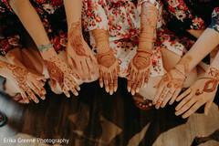 Indian bridal party showing their mehndi art
