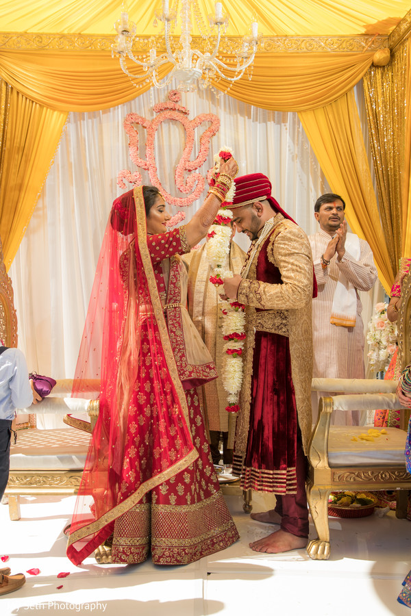 Indian bride and groom exchanging garlands rituals.