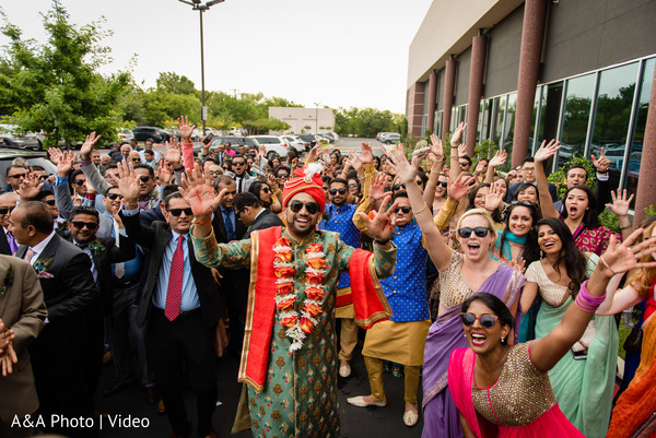 Indian groom posing wth guests during the baraat
