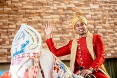 Charming Indian groom on his white baraat horse.