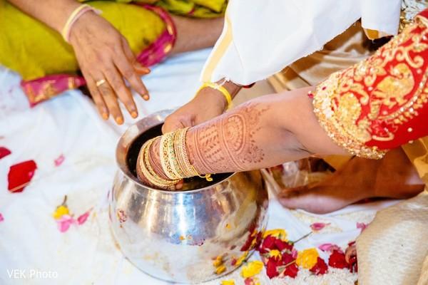 Closeup capture of Indian bride and groom's hands in ceremony jar.