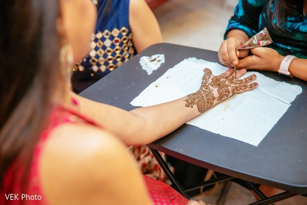 Indian bride getting her hands with henna art.