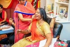 Joyful Indian bride with turmeric paste on her face.