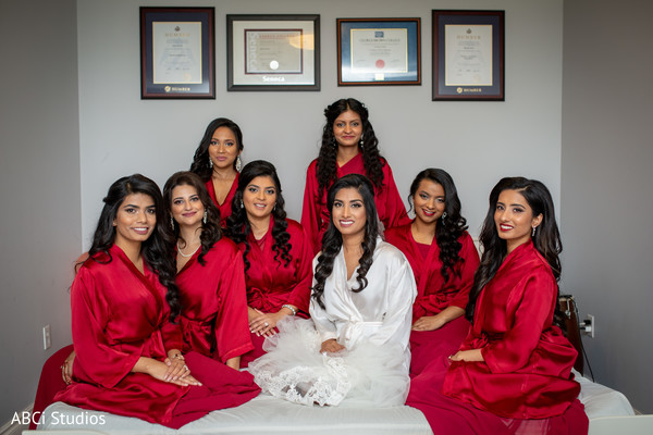 Joyful Indian bride with bridesmaids getting ready for wedding.