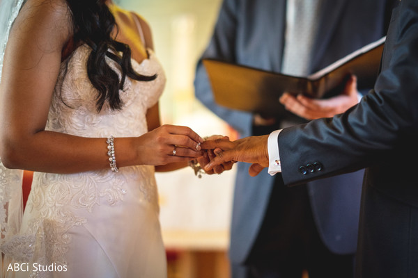 Indian bride putting the wedding band to groom capture.