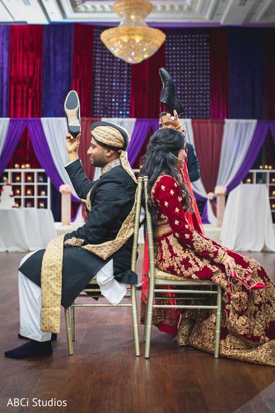 Indian lovebirds at wedding reception shoe game.