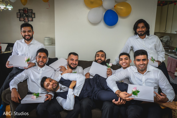 Indian groomsmen getting their boutonniere and presents.