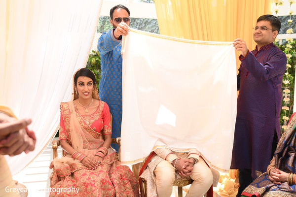 Indian groom covered with antarpat at ceremony.