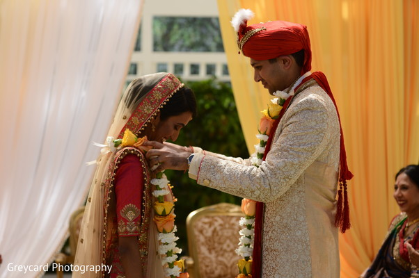 Indian groom putting flower garland to bride.