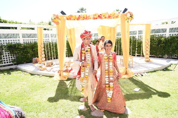 Indian couple walking hand in hand from ceremony.