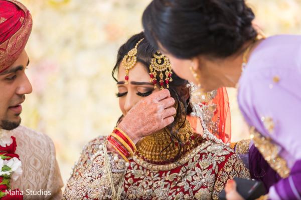 Emotional capture of Indian bride at ceremony.