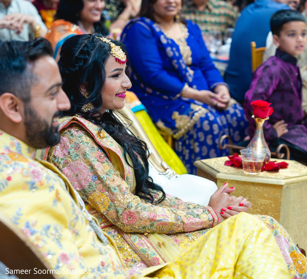 Indian bride and groom listening to the guests