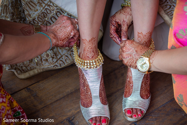 Indian bride putting her ankle jewelry
