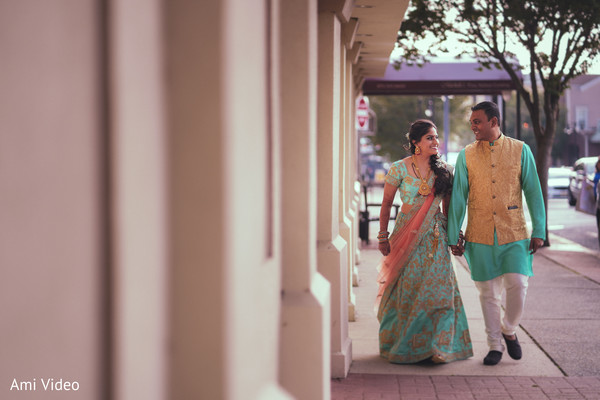 Indian couple walking holding hands.