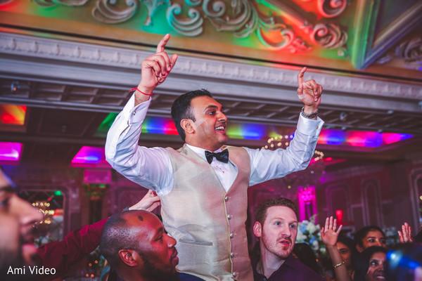 Indian groom being lifted by groomsmen.