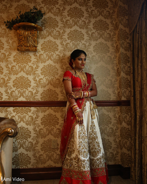 Indian bride posing on her ceremony outfit.