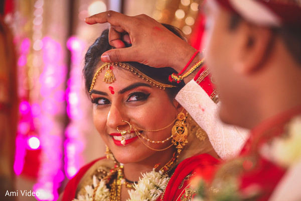 Indian bride getting the kumkum mark from groom ritual.