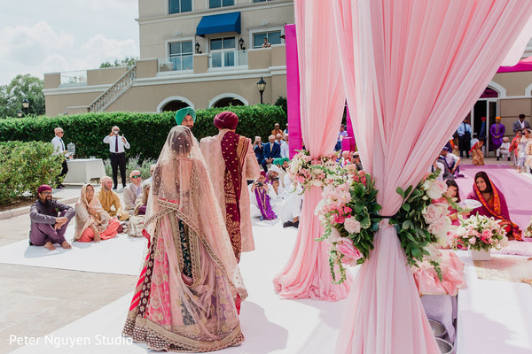 Indian bride and groom walking by the mandap