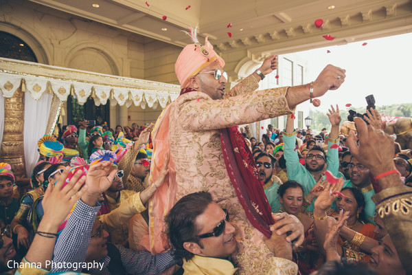 Indian groom being lifted during the baraat