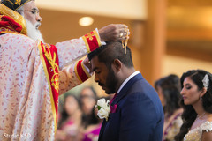 Charming Indian groom receiving blessings from priest.