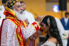 Charming Indian bride receiving blessings from priest.