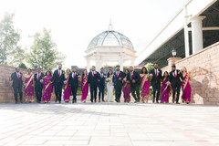 Lovely Indian couple posing outdoors with bridesmaids and groomsmen.