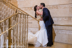 Indian bride and groom kissing during pictures