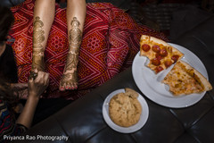 Indian bride being assisted with the mehndi design