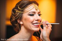 Makeup artist assisting the bride