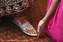 Indian bride being assisted with feet Mehndi