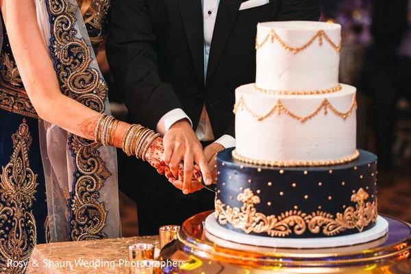 Beautiful indian wedding cake being cut