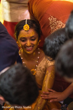 Indian bride  getting Turmeric paste on her arms.