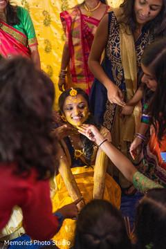 Indian bridesmaids putting turmeric paste on bride's face.