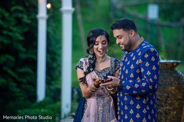 Indian groom admiring bridal henna art.