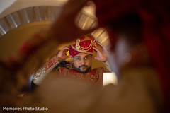 Charming Indian groom putting his turban on.