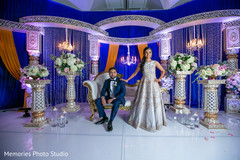 Fabulous Indian bride and groom posing at reception stage.