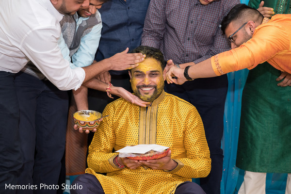 Indian groom getting the turmeric paste on.