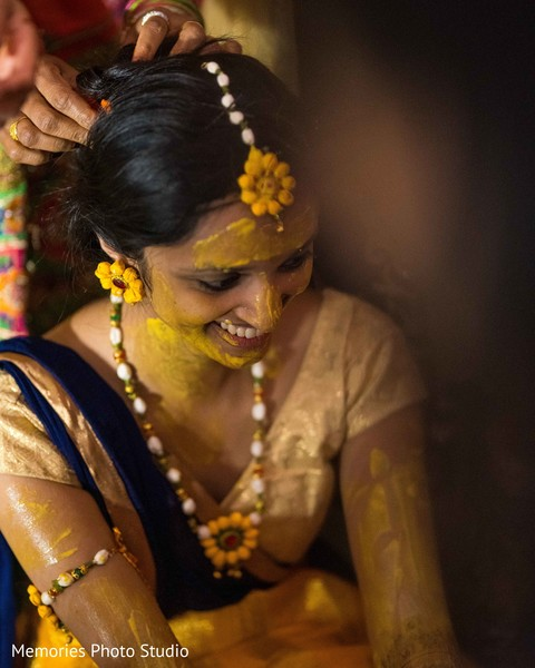 Indian bride smeared all over with turmeric paste.