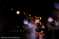 Romantic capture of Indian bride and groom at sangeet dance.